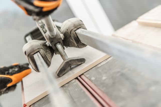 Ceramic Tiles Cutter and Cutting Process Closeup Photo. Tile Preparation.