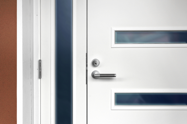 Modern white front door with metal fixture handle and glass windows